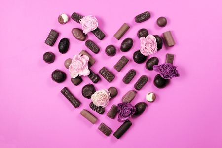 Saint Valentines day concept. Chocolate candies and roses on pink background