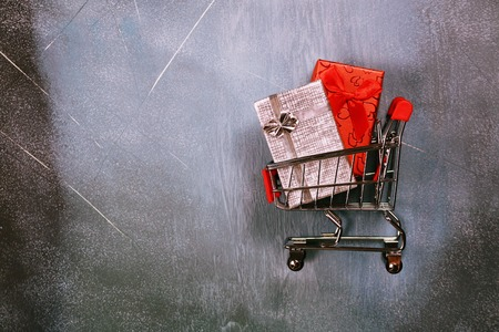 Online shopping concept, shopping cart and gift boxes on textured background