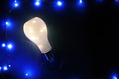 Glowing lightbulb on black background