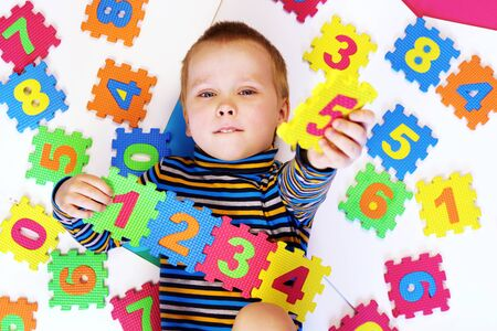 Early childhood education, preschool and kids game concept. Happy baby boy learning to count.