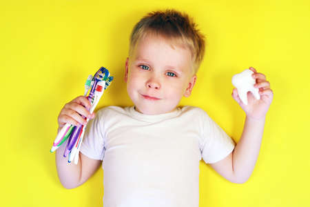 Cute boy child kid holding a toothbrushes and a tooth toy on yellow background, copy space. Teeth cleaning, health care, dental hygiene concept