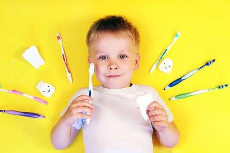 Cute boy holding a toothbrush and a tooth toy surrounded by toothbrushes on yellow background top view, teeth cleaning concept, baby hygiene concept