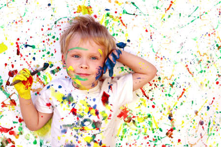 Happy cute dirty boy child playing with paint on colorful background. Drawing concept