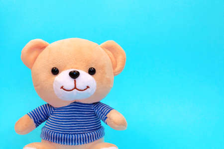 Teddy bear in striped sweater isolated on blue background with copy space