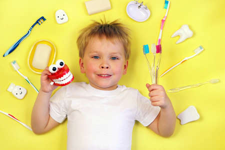 Cute boy child kid holding toothbrushes and toy teeth on yellow background. Teeth cleaning, oral care, dental hygiene concept , top view