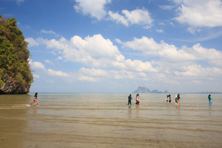 Happy muslim girls or teens enjoying in the sea during summer vacation. Clouds and light blue sky, cliff and sea background. Hat Chao Mai National Park, Trang Province, Thailand. Stock Photo