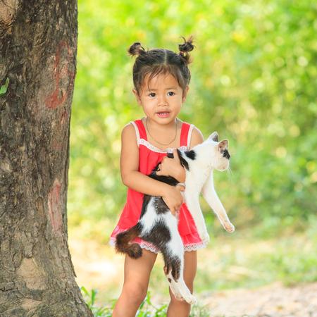 Champasak, Laos – OCTOBER 24, 2010: Little Laos girl hugging cat in her arms. Pakse District.