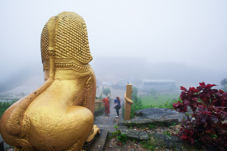Giant gold statue of Singha Khmer, monk, and tourist in the mist. Wat Sampov Pram, Preah Monivong Bokor National Park, Kampot, Cambodia. Stock fotó