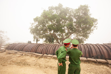 Young couple Vietnamese soldier taking photo of the bunker of the French General De Castries, the most important camp of the French colonists during the first Indochina War in 1954. Dien Bien Phu, Vietnam. White fog background. Stock Photo