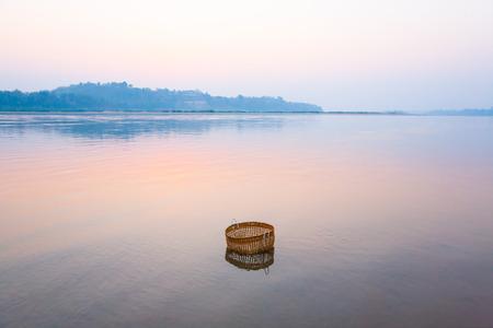 Beautiful gently river at sunrise, bamboo basket for washing vegetable is dip in Mekong River. Thai-Laos border background. Chiang Khong District, Chiang Rai, Thailand. Banco de Imagens
