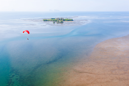 Aerial view, paraglider flying over the island in summer season. Red paramotor foreground. Hat Chao Mai National Park. Trang Province, southern Thailand. Stock Photo