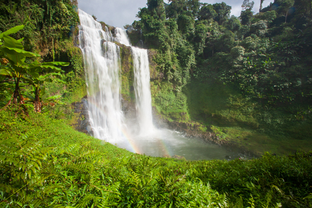 Great waterfall scenery with a rainbow. Tad Yuang, dramatic waterfall drops 40 metres over a cliff and tropical forest. Bolaven Plateau, Paksong, Laos. Rainy season.