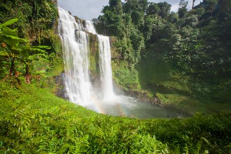 Tolle Wasserfalllandschaft mit einem Regenbogen. Tad Yuang, dramatischer Wasserfall fällt 40 Meter über eine Klippe und einen tropischen Wald. Bolaven-Plateau, Paksong, Laos. Regenzeit.