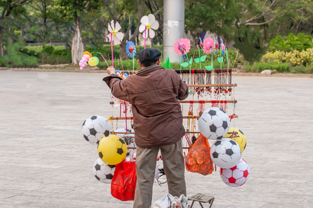 Chinese old man street vendor seller ball and other toys in the Public garden of Nansa, Yunnan, China. Football concept. Stock Photo