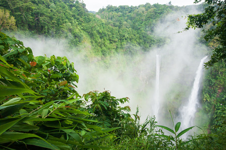 Great waterfall scenery in the mist. Tad Fane is a picturesque twin set of waterfall spilling 120 meters down into a deep gorge, rainforest spot is part of a big national park. Bolaven Plateau, Paksong, Laos. Rainy season.