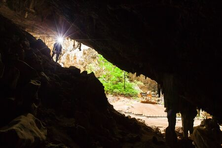 Young man exploring mystery cave with a torch, Phraya Nakhon Cave is a large cave which has a hole in the ceiling allowing sunlight to penetrate, the cave is most popular attraction is a pavilion cons 스톡 콘텐츠