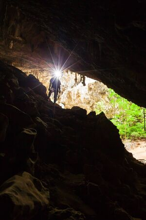 Young man exploring mystery cave with a torch, Phraya Nakhon Cave is a large cave which has a hole in the ceiling allowing sunlight to penetrate, the cave is most popular attraction at Prachuap Khiri  스톡 콘텐츠