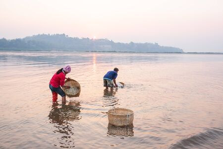 Thai farmer washing Bean Sprouts in Mekong River at sunrise. Bean Sprouts in bamboo basket. Organic vegetables. Thai-Laos border background. Chiang Khong District, Chiang Rai, Thailand. Simple life. Stock Photo