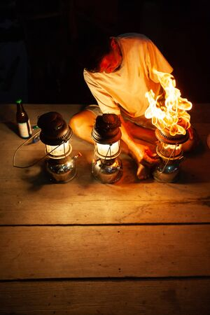 Fantastic fire flames, the old man with three vintage kerosene pressure lanterns on wooden at night, beautiful brightly burning gas. The Lamplighter. Copy space. Shallow dept of field. Rural of Thailand.