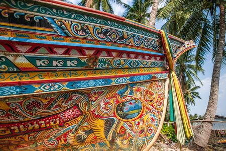 Beautiful Kolae boat, traditional Thai-Malayu fishing boat. Colorful mural painting and color cloth hanging on the bow of the boat. Coconut trees and local village backgrounds. Sai Buri, Pattani, Thailand. Soft sunlight.