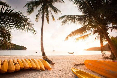 Beautiful time, sun setting over the sea. Yellow Sea Kayaks on sand beach and coconut trees foregrounds, local fishing boat and yacht backgrounds. Summer season. Mu Koh Ang Thong National Park, Surat Thani, Thailand. Warm tone. Stock Photo