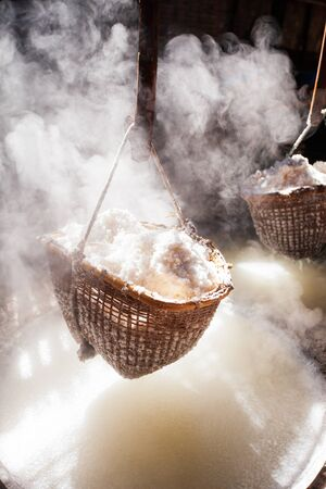 Ancient method of boiling brine into pure salt in Bo Kluea, Nan, Thailand. Beautiful smoke, sunlight shines down around ancient salt pits and bamboo basket. Traditional rock salt. Salt culture. History of salt.