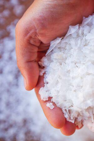 Pure white crystals salt, rock salt in women hands on crystals background. Top view, close-up. Traditional rock salt making of Bo Kluea, Nan, Thailand. Ancient salt pits. Salt culture. History of salt. Selective focus.