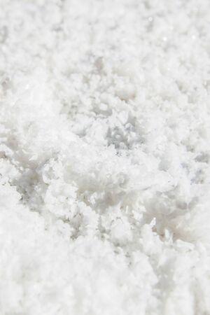 Pure white crystals salt, rock salt on the ground. Top view, close. Traditional rock salt making of Bo Kluea, Nan, Thailand. Ancient salt pits. Salt culture. History of salt. Full frame. Bright sunlight.