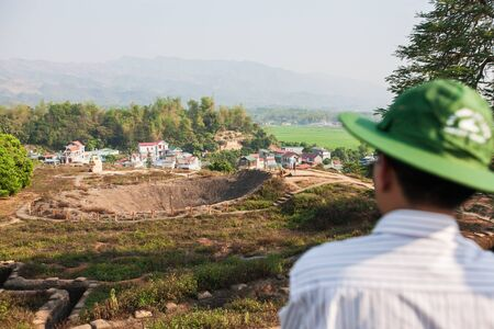 Crater of A1 hill, the most important camp of the French colonists in Dien Bien Phu during the first Indochina War in 1954. Village and paddy fields backgrounds. Dien Bien, Vietnam.