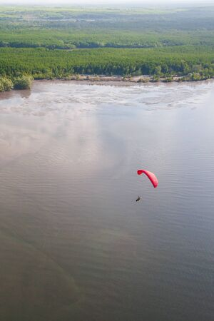 Aerial view, red paraglider or paramotor flying over the sea, green mangrove island backgrounds. Hat Chao Mai National Park. Trang Province, south Thailand. Soft sunlight. Summer season. Copy space. Stok Fotoğraf