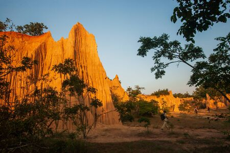Group of tourists at ancient scenic landscape at sunset. The Sao Din Na Noi site displays picturesque scenery of eroded sandstone pillars, similar Canyon. Fantastic columns and cliffs texture, tropical forest foregrounds. Warm tone, soft sunset. Nan, Thailand. Stock fotó