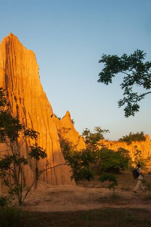 Tourists at ancient scenic landscape at sunset. The Sao Din Na Noi site displays picturesque scenery of eroded sandstone pillars, similar Canyon. Fantastic columns and cliffs texture, tropical forest foregrounds. Warm tone, soft sunset. Nan, Thailand. Stock fotó