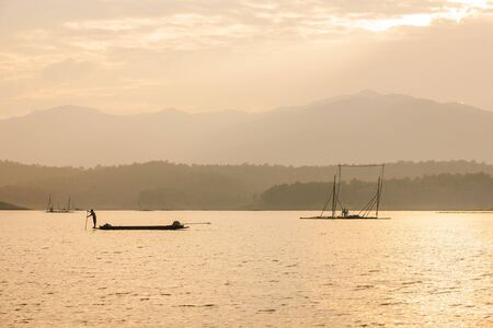 Fisherman on fishing boat in The Sirikit Dam, raft dip net and sunset sky backgrounds. Golden sun setting shines down around the lake. Beautiful glistening. Summer season. Silhouette. Warm tone. Nan, Thailand. 版權商用圖片