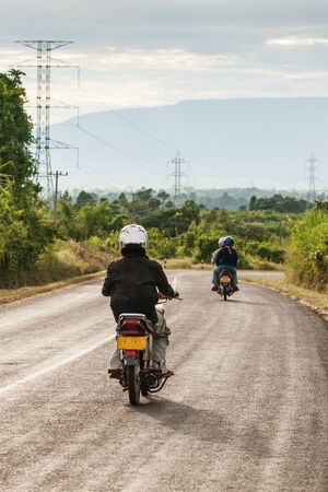 Motorcycle travels on the National Highway T 16 from Salavan to Pakse, Laos. Asphalt road on Bolaven Plateau at evening, Laos people returning home after work. Summer season. Transportation.