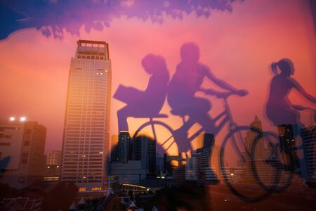 Mirror image, internal view of a book shop and mirrored picture of children ride bike in foregrounds. Bangkok City at twilight backgrounds. Beautiful light and sky. abstract futuristic cityscape. Thailand. City art concept.
