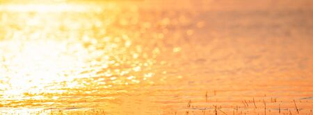 Panorama view. Colorful texture and backgrounds water of lake in sunset light. Beautiful glittering water, golden and silver sparkling on the lake. Rural of Thailand. Summer season. Warm tone. Copy space.