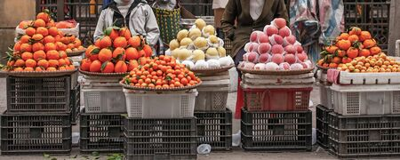 Fruit street vendors at Lao Kai, Vietnam-China border. Vietnamese woman street venders with orange, apple, chinese pear and Mangoes. Colorful of fruits in winter season. Vietnam. Shallow dept of field. Street food concept. Panorama view. Фото со стока