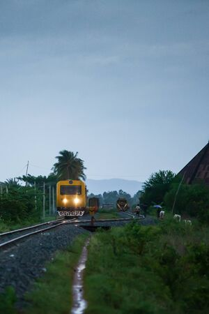 Two passenger train passing through small railway junction in rainy evening, countryside of Battambang Province, Cambodia. Transportation. Shallow dept of field. Noise, Grain.