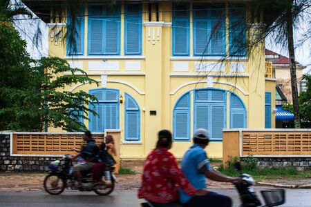Khmer people riding motorcycle pass old french colonial building. Scenic landscape town of Kampot, South Cambodia, ancient colonial architecture. Long exposure. Selective focus. Фото со стока