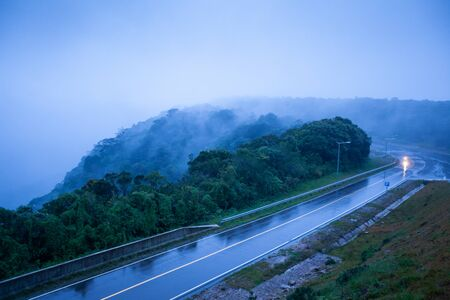 Mountain road in foggy dusk, motorcycle riding on asphalt road through the mountain top of Phnom Bokor Mountain in rainy day, Preah Monivong Bokor National Park, Kampot, top tourist attractions in Cambodia. Shallow dept of field. Blue tone.