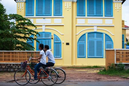 Couple Khmer teens riding bicycle pass old french colonial building. Scenic landscape town of Kampot, South Cambodia, ancient colonial architecture. Long exposure. Selective focus.