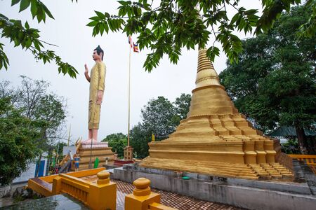 Ancient golden pagoda and buddha statue at Wat Phnom Yat, Pailin Province, West Cambodia, the temple built by Shan migrants from Myanmar in 1922. Shallow dept of field. The temple is open to the Public.