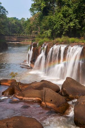 Gently rainbow over tropical waterfall. Tad Pha Suam waterfall in rainy season. Beautiful sandstone and gently waters falling off the cliff, bamboo bridge backgrounds. Bolaven Plateau, Pakse, Laos. Long Exposure. Bright sunlight. Stock fotó