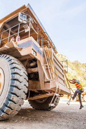 Male driver walks up the stairs of large quarry dump truck at open space, production useful minerals, to transport coal from open pit in mountainous area.