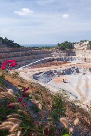 Aerial view of cement mining quarry with machinery at work. Fantastic landscape of open pit and limestone layers in rocks. Beautiful wild flowers at mine site and light blue sky. Thailand.