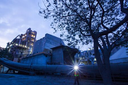 Cement plant factory manufacturing at dusk, sparks of worker with headlamp flashlight during working overtime. Industrial worker concept.