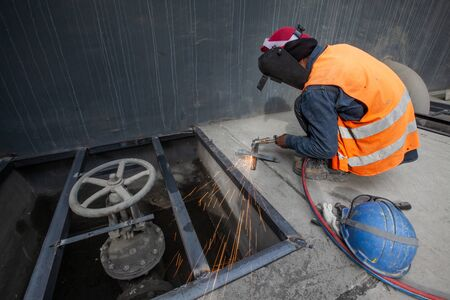 Male welder is welding new steel grate, arc welding process with sparks. Industrial worker concept. Long exposure. Stock Photo