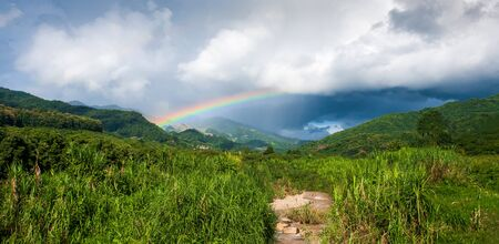 Panorama view, colorful rainbow over tropical mountain valley in the rain, scenic landscape green forest and stream in countryside. Stok Fotoğraf