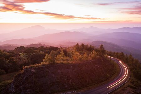 Beautiful mountain road at sunrise, curve asphalt road with light trail from headlights leading through mountain range, colorful clouds and early morning sky. Doi Inthanon, Chiang Mai, Thailand. Long exposure.