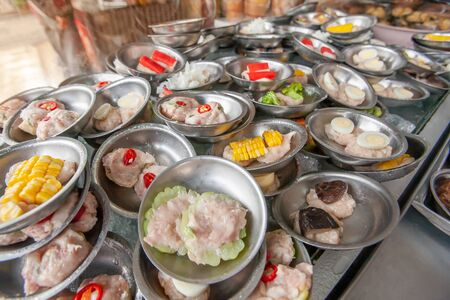 A various of Dim Sum streamer dumplings served on small stainless-steel plates in a local chinese restaurant at Betong, Yala, near the Malaysian border, top tourist attractions in Southern Thailand. Stock Photo